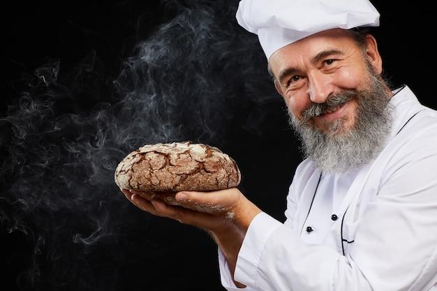 黒に対して焼きたてのパンを持って笑顔のパン屋