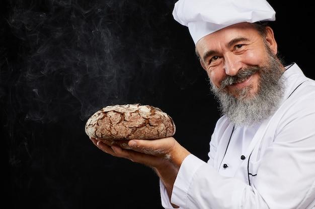 黒に対して新鮮なパンを保持しているひげを生やしたベイカー