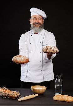 伝統的なパンを持って笑顔のベイカー