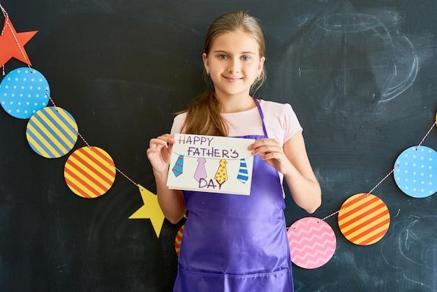 Счастливая девочка-подросток держит открытку на день отцов