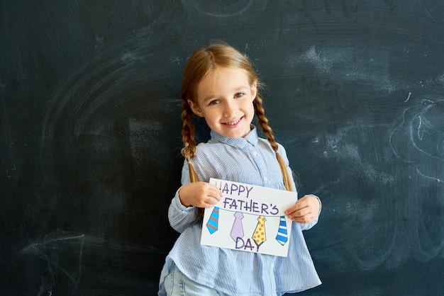 Счастливая маленькая девочка держит открытку на день отцов