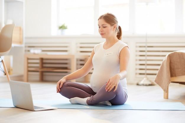 Беременная женщина практикует домашнюю медитацию