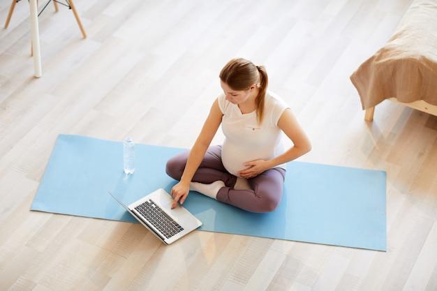 Беременная женщина смотрит видео с тренировки