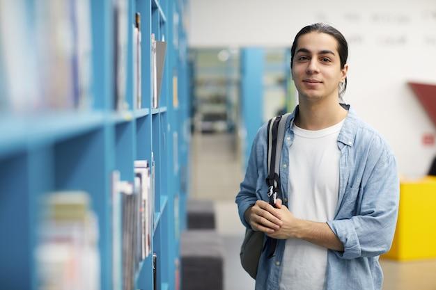 Студент позирует в библиотеке колледжа