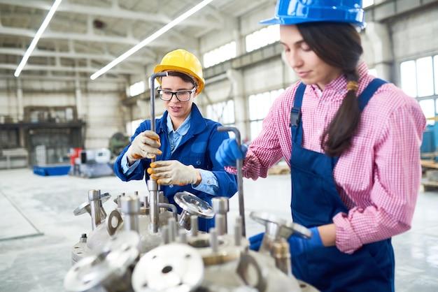 Работники фабрики, использующие шестигранные ключи