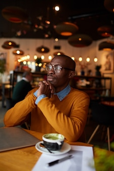 Задумчивый афроамериканец в кафе