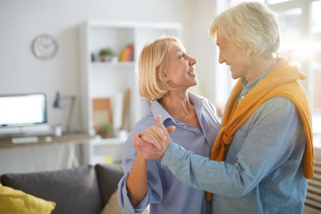 家で踊る年配のカップルを愛する