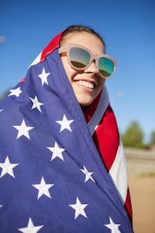 Счастливая американская девушка в солнечных очках