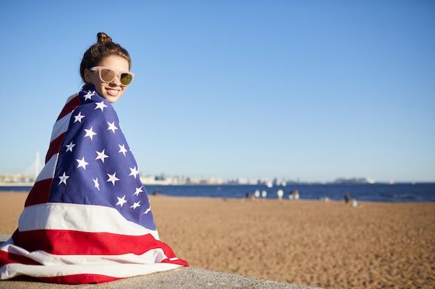Счастливая женщина в большом американском флаге