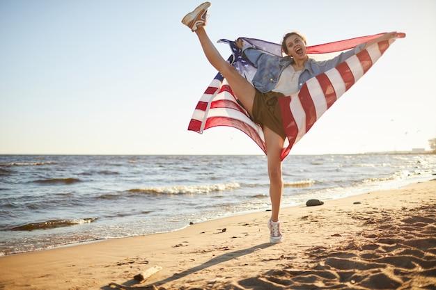 Взволнованная гибкая женщина с флагом сша
