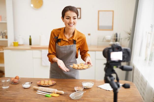 若い女性が台所で焼くビデオを撮影