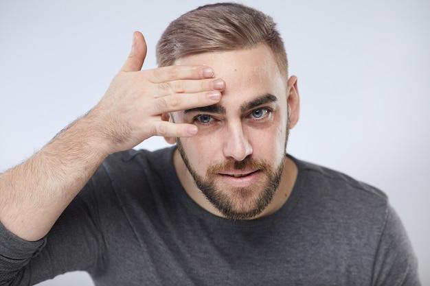 Молодой человек, применяя крем для лица
