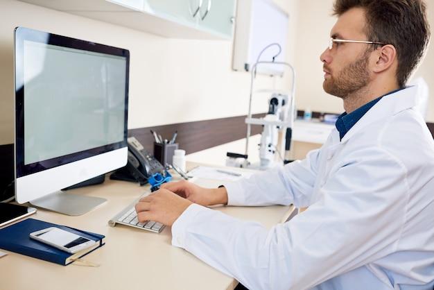 オフィスでコンピューターを扱う医師