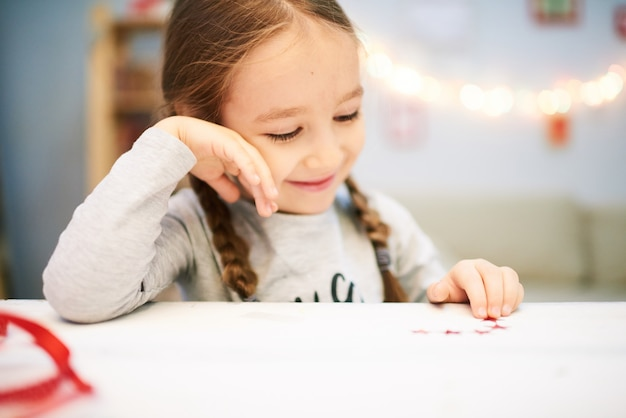 Улыбающаяся маленькая девочка, завернутая в изделие кустарного промысла
