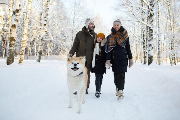 Семья гуляет с собакой зимой