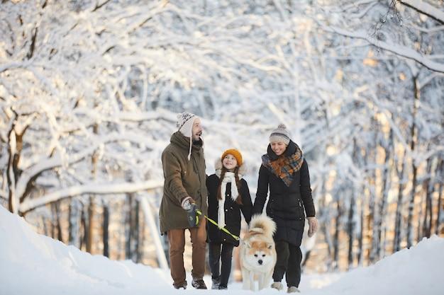 Счастливая семья гуляет с собакой в парке