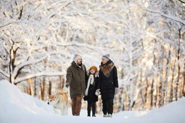 Семья гуляет с собакой в зимнем парке