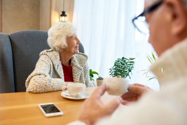 Задумчивая старшая женщина за столом в кафе