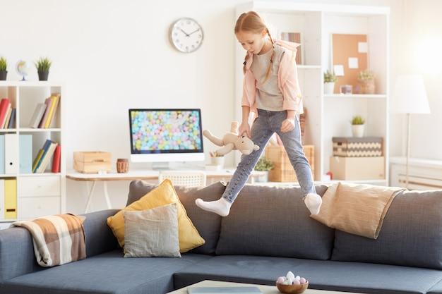 ソファでジャンプ遊び心のある女の子