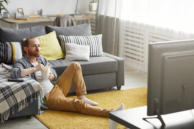 Человек смотрит телевизор в холостяцкой колодке