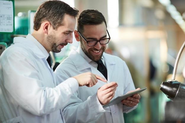 Два заводских рабочих в лабораторных халатах