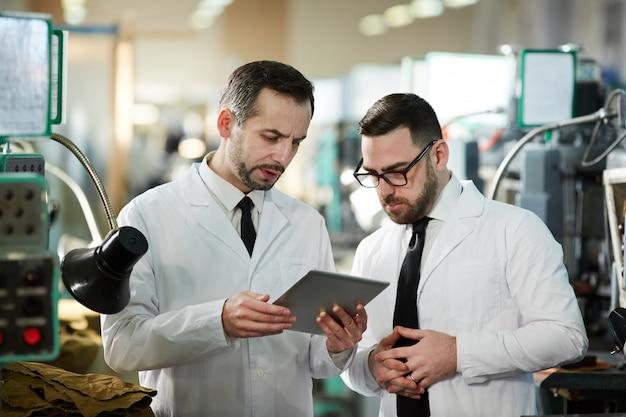 Два рабочих на современной производственной фабрике