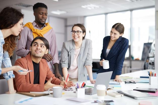 Улыбающаяся творческая команда, работающая в офисе