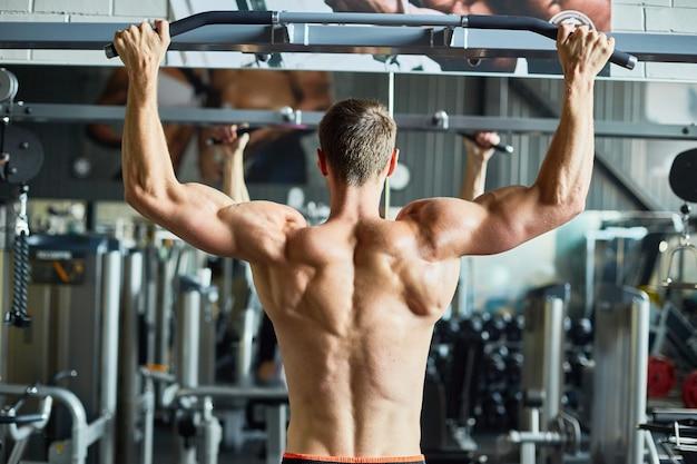 Мускулистая голая спина красивого мужчины в тренажерном зале