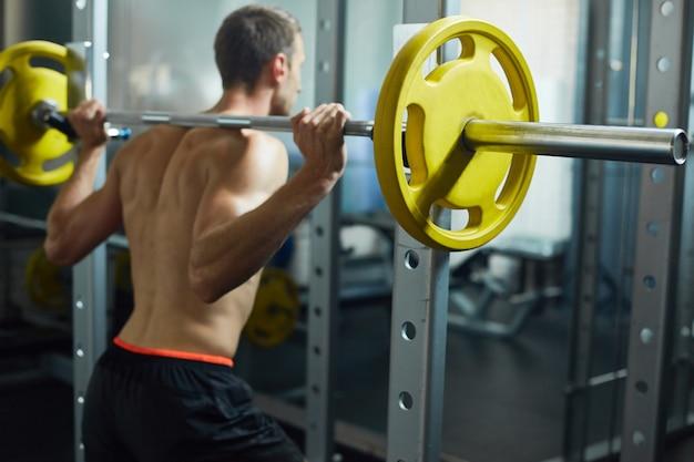 Тяжелая атлетика молодого человека в спортзале