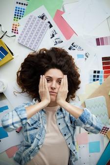 Улыбающаяся молодая женщина в творческом беспорядке