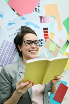 Улыбающаяся деловая женщина читает книгу на полу