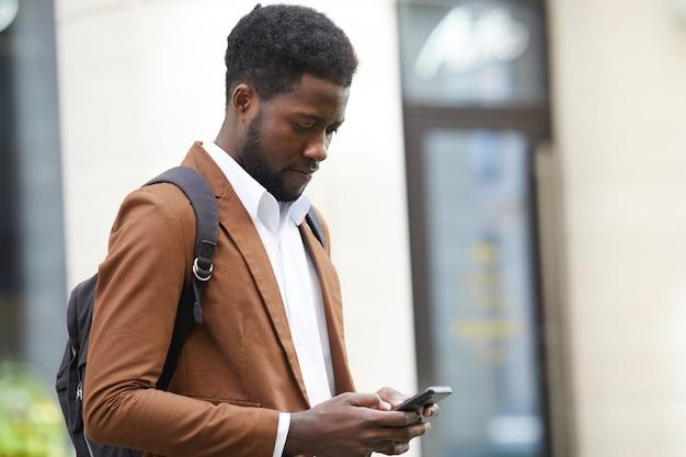 Современный африканский человек с помощью смартфона на открытом воздухе