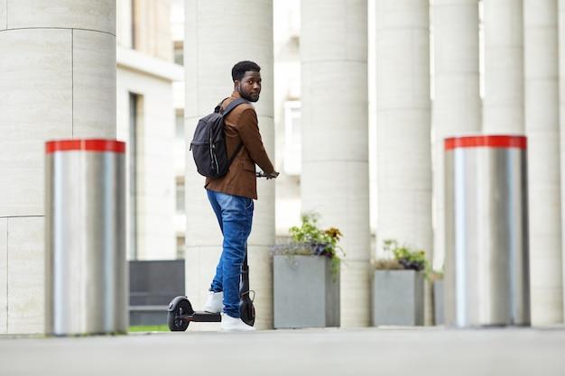 Современный афроамериканец человек верхом на скутере в городе