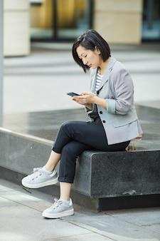 市でスマートフォンを使用して現代のアジアの女性