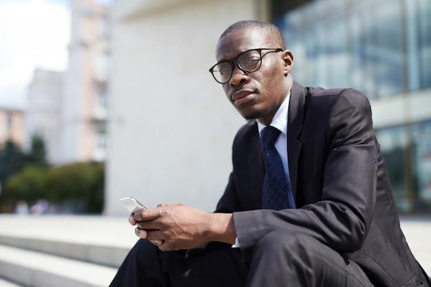 Афро-американский бизнесмен сидит на ступеньках