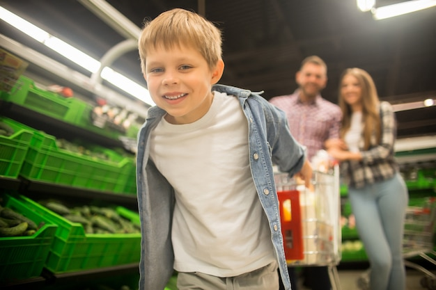 スーパーでカートを引っ張る幸せな少年