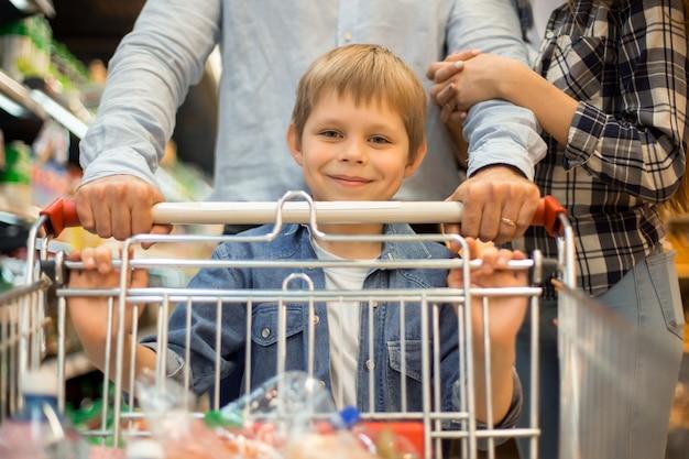 両親と幸せな小さな男の子の食料品の買い物