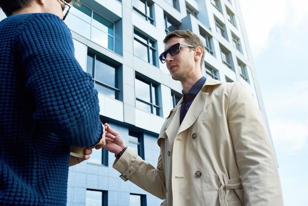 Успешный предприниматель разговаривает с коллегой на свежем воздухе
