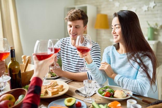幸せな友達が感謝祭のディナーで乾杯