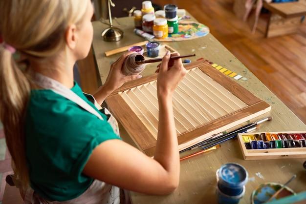 Молодая женщина красит мебель в художественной студии