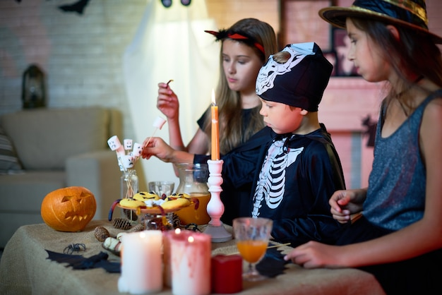 Дети едят закуски на хэллоуин