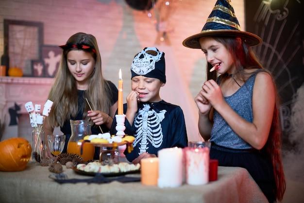 Дети едят сладости на хэллоуин