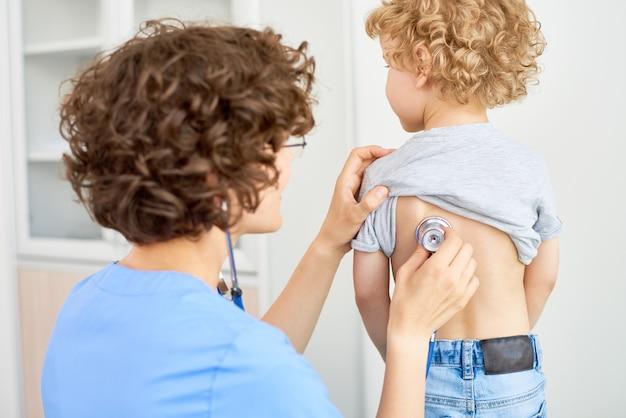 男の子の呼吸に耳を傾ける小児科医
