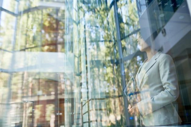 Мечтательная деловая женщина, наслаждаясь видом за окном
