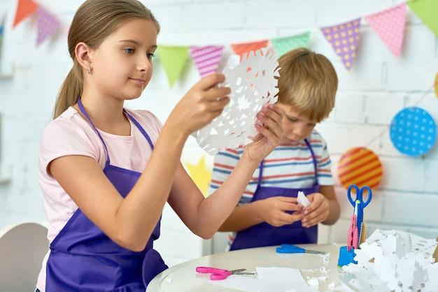 Дети, делающие рождественские украшения