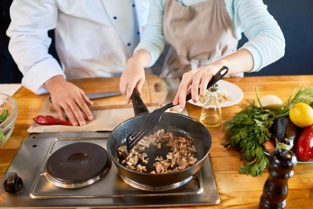 料理教室でキノコを揚げる