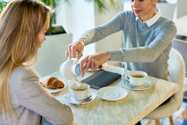 Две молодые женщины наслаждаются завтраком в кафе