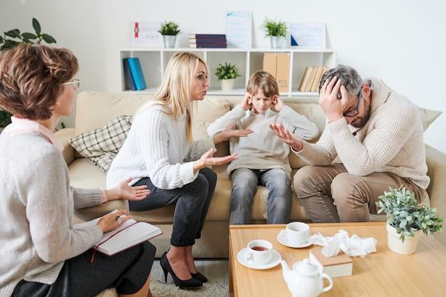 Грустный сын, закрывающий уши, а родители ссорятся во время сеанса терапии