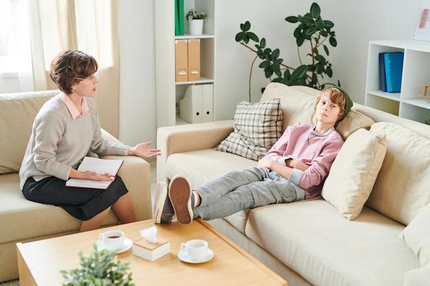 Грустный подросток сидит на сеансе терапии