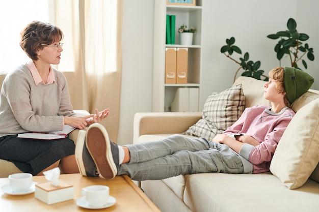 Зрелый психиатр разговаривает с подростком, игнорируя ее